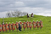 Roman soldiers of Ermine Street Guard, in line abreast with shields and stabbing swords, cavalry in support, Birdoswald Roman Fort, Hadrians Wall, Northumbria, England, United Kingdom, Europe