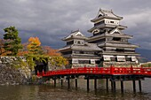 Matsumoto-jo (Matsumoto Castle), three-turreted donjon built in 1595 in contrasting black and white, surrounded by a moat with access across ornate red bridges, Matsumoto, Nagano Prefecture, Central Honshu (Chubu), Japan, Asia