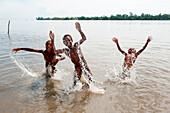 Cheerful children swim and splash in water, Kopar, East Sepik Province, Papua New Guinea, South Pacific