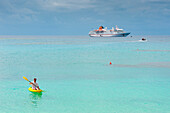 Man paddles kayak off beach at Sandy Beach Resort with expedition cruise ship MS Hanseatic (Hapag-Lloyd Cruises) at anchor behind, Foa Island, Ha'apai Group, Tonga, South Pacific