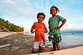 Young boy and girl in canoe on beach, Biak, Papua, Indonesia, Asia