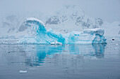 A blue iceberg is reflected in the water with a Zodiac dinghy from expedition cruise ship MS Hanseatic (Hapag-Lloyd Cruises) in distance, Paradise Bay (Paradise Harbor), Danco Coast, Graham Land, Antarctica