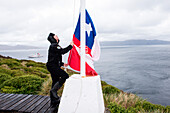 Armada de Chile officer raises Chilean national flag at Cape Horn weather station, Cape Horn, Cape Horn National Park, Magallanes y de la Antartica Chilena, Patagonia, Chile, South America