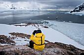 Crew member of expedition cruise ship MS Hanseatic (Hapag-Lloyd Cruises) on mountainside, Neko Harbour, Graham Land, Antarctica