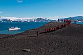 Passagiere von Expeditions-Kreuzfahrtschiff MS Hanseatic (Hapag-Lloyd Kreuzfahrten) trekken durch Vulkanlandschaft in majestätischer Bergkulisse, Telephone Bay, Deception Island, Südshetland-Inseln, Antarktis