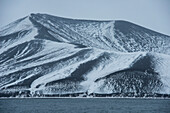 Snow on the volcanically formed hills creates a graphic, monochrome landscape, Deception Island, South Shetland Islands, Antarctica