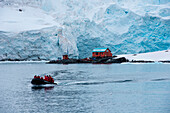 Zodiac dinghy from expedition cruise ship MS Hanseatic (Hapag-Lloyd Cruises) with Base Almiranta Brown (Argentina) in icy landscape, Paradise Bay (Paradise Harbor), Danco Coast, Graham Land, Antarctica