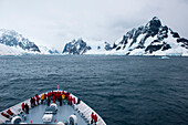 Passengers on bow of expedition cruise ship MS Hanseatic (Hapag-Lloyd Cruises) in Lemaire Channel, one of the most beautiful waterways on the northern Antarctic Peninsula and is one of many highlights of a cruise in this harsh area, Lemaire Channel, near