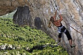 A woman on an overhanging traverse climb on the famous limestone cliffs of the Mascun Canyon, Rodellar, Sierra de Guara, Aragon, southern Pyrenees, Spain, Europe
