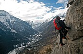 A man on a via ferrata route high above the tiny village of Fressinieres, near Briancon, Ecrins Massif, western Alps, France, Europe