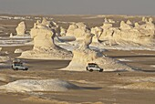 Jeeps passing the wind-eroded sculptures of calcium rich rock in The White Desert near Bahariya, Egypt, North Africa, Africa