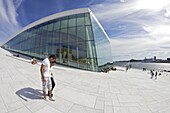 Young couple walking outside the Oslo Opera house exterior in summer sunshine, city centre, Oslo, Norway, Scandinavia, Europe