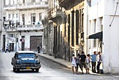 Street scene showing old American car operating as taxi for local people and a queue of people outside a shop, Havana, Cuba, West Indies, Central America