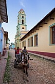 Two men on horse-drawn cart travelling along a quiet street in Trinidad, Sancti Spiritus Province, Cuba, West Indies, Caribbean, Central America