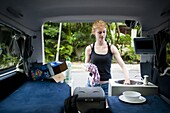 Woman washing up in a campervan, Byron Bay, New South Wales, Australia, Pacific