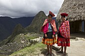 Traditionally dressed children looking over the ruins of Machu Picchu, UNESCO World Heritage Site, Vilcabamba Mountains, Peru, South America