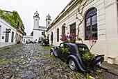 Old car turned into planter on cobblestone street in Colonia del Sacramento, Uruguay, South America