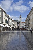 Foot worn glossy roadway in the main street dominated by the clock tower. medieval city of Dubrovnik, UNESCO World Heritage Site, Croatia, Europe