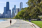 Jogger on North Avenue Beach with John Hancock Center and city skyline behind, Chicago, Illinois, United States of America, North America