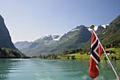 Sailing on the green lake and Norwegian flag, Olden, Fjordland, Norway, Scandinavia, Europe