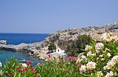 A small white church and fising boat in St. Paul's Bay near Lindos, Rhodes, Dodecanese Islands, Greek Islands, Greece, Europe