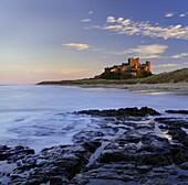 Bamburgh Castle bathed in warm evening light, Bamburgh, Northumberland, England, United Kingdom, Europe