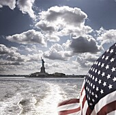 View of Statue of Liberty from rear of bot with Stars and Stripes flag, New York, United States of America, North America