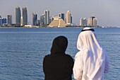Man and woman in traditional dress looking across Doha Bay from the Corniche to the new city skyline and West Bay business and financial district, Doha, Qatar, Middle East