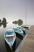Pleasure boats moored at Llangorse Lake on a misty morning, Brecon Beacons National Park, Powys, Wales, United Kingdom, Europe