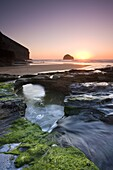 Water channel flowing beneath natural rock arch at Trebarwith Strand beach in Cornwall, England, United Kingdom, Europe
