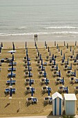 Quiet beach with beach hut, one umbrella open, and two people at waters edge, Jesolo, Veneto, Italy, Europe