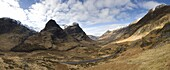 Panoramic view of Glencoe showing The Three Sisters of Glencoe mountains and the A82 trunk road winding down through the glen towards Glencoe Village, near Fort William, Highland, Scotland, United Kingdom, Europe