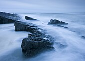 Swirling tide around jagged rocks on Spekes Mill Mouth beach, Hartland, Devon, England, United Kingdom, Europe