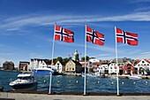 Norwegian flags and historic harbour warehouses, Stavanger, Norway, Scandinavia, Europe
