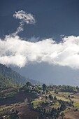 Village of Shingyer against a dramatic backdrop of mountains and clouds, Phobjikha Valley, Bhutan, Himalayas, Asia