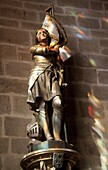 Statue of St. Joan of Arc with coloured light from stained glass, Church of Notre Dame, Vitre, Brittany, France, Europe
