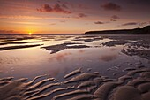 Sunset over the Atlantic Ocean, from the sandy shores of Bedruthan Steps beach, Cornwall, England, United Kingdom, Europe