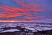 Fiery sunset over a snow covered Gormire Lake from Sutton Bank on the edge of the North Yorkshire Moors, Yorkshire, England, United Kingdom, Europe