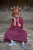 Young Buddhist monk holding traditional carved wooden mask to his face at the Tamshing Phala Choepa Tsechu, near Jakar, Bumthang, Bhutan, Asia