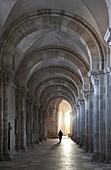 Interior north nave aisle with priest walking away, Vezelay Abbey, UNESCO World Heritage Site, Vezelay, Burgundy, France, Europe
