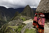 Traditionally dressed children looking over the ruins of the Inca city of Machu Picchu, UNESCO World Heritage Site, Vilcabamba Mountains, Peru, South America