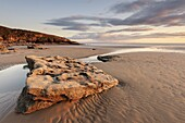 Sunset over rocks with flowing water at Dunraven Bay, Southerndown, Wales