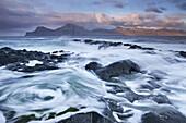Surging waves break over the rocky shores at Gjogv on the island of Eysturoy, Faroe Islands, Denmark, Europe