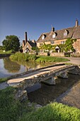 Stone footbridge and cottages in the picturesque Cotswolds village of Lower Slaughter, Gloucestershire, England, United Kingdom, Europe