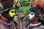 Tribesmen puting colour on their faces to celebrate the traditional Sing Sing in Paya in the Highlands, Papua New Guinea, Pacific