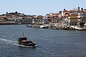 A boat cruises on the River Douro, past the Ribeira District, UNESCO World Heritage Site, Porto, Douro, Portugal, Europe