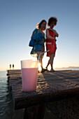 Drink on a wooden jetty, two women walking past in the background, Playa de Muro beach, Alcudia, Mallorca, Balearic Islands, Spain