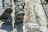 Person standing on step tread, next to sign Genusswandl, Hochthronklettersteig, fixed rope route Hochthron, Untersberg, Berchtesgadener Hochthron, Berchtesgaden Alps, Upper Bavaria, Bavaria, Germany