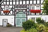 Half-timbered house in the village Kirchveischede, near Lennestadt, Rothaargebirge, Sauerland region, North Rhine-Westphalia, Germany