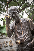 bronze statue of tourist filming and taking photographs in the colonial quarter at Downtown Guangzhou, Guangdong province, Pearl River Delta, China